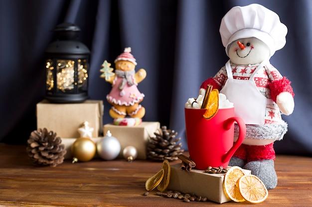 Un bonhomme de neige et une tasse givrée rouge avec des guimauves et de la cannelle sur fond de noël