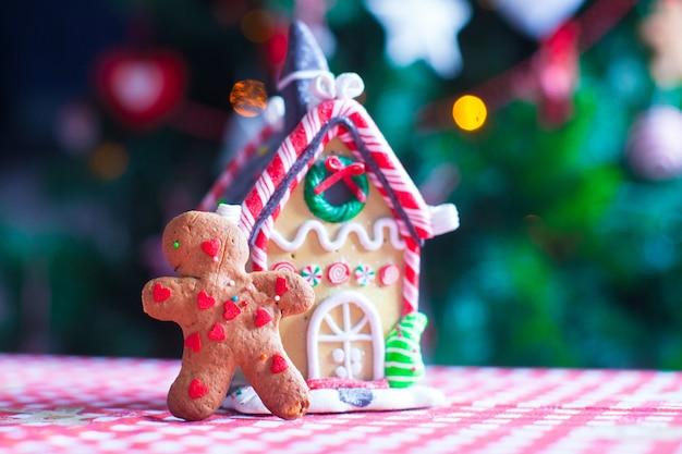 Bonhomme en pain d'épice devant sa maison de bonbons au gingembre et lumières de l'arbre de noël