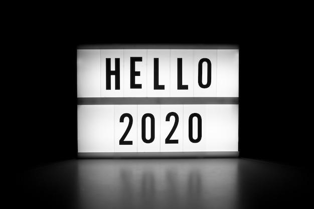 Bonjour 2020 - texte sur une lightbox d'affichage dans l'obscurité. concept de nouvel an