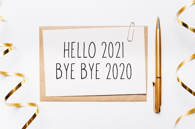 Bonjour 2021 bye bye 2020 note avec enveloppe, stylo, cadeaux et ruban d'or sur une surface blanche. joyeux noël et nouvel an concept