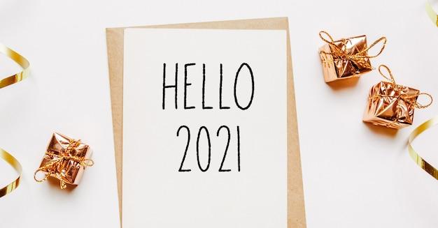 Bonjour 2021 note avec enveloppe, cadeaux et ruban d'or sur blanc