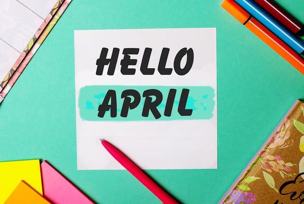 Bonjour avril écrit sur un fond turquoise près d'autocollants, blocs-notes et marqueurs lumineux