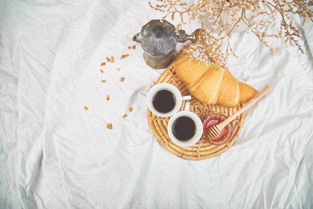 Bonjour. deux tasses de café avec croissant et confiture.