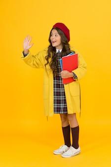 Bonjour. enfant joyeux prêt pour l'année scolaire. éducation. enfance heureuse. cahiers pour apprendre en classe. retour à l'école. une fille rétro porte un uniforme et un béret parisien. mode scolaire pour enfants.