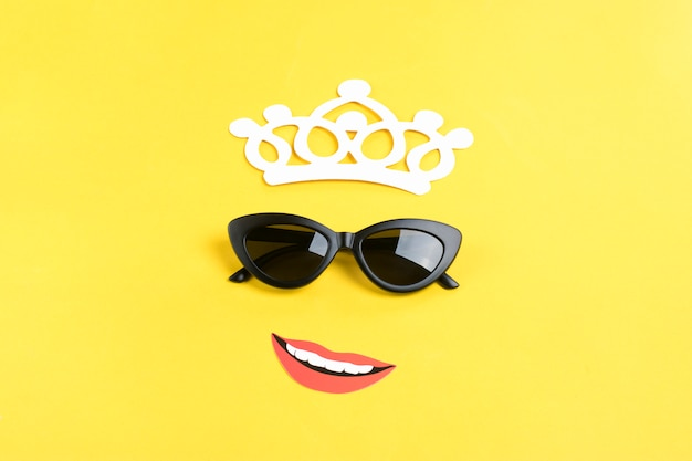 Bonjour l'été, le soleil avec des lunettes de soleil noires élégantes, une couronne, une bouche souriante sur jaune