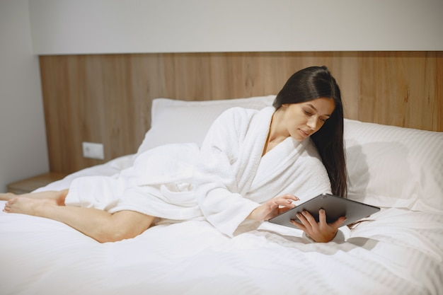 Bonjour. femme dans un lit. dame dans la chambre. brunette avec tablette.