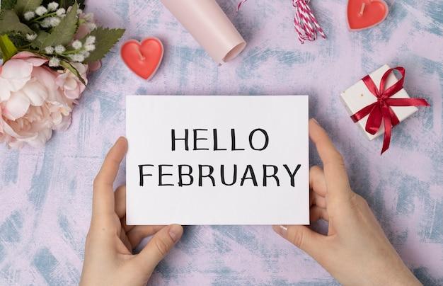 Bonjour février mot sur boîte à lumière avec bouquet de fleurs roses sur fond de bois