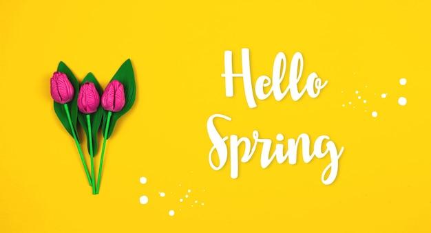 Bonjour fond coloré jaune de printemps, composition à plat avec fleurs décoratives, tulipes roses et violettes pour les vacances internationales, bannière et photo de l'espace de copie