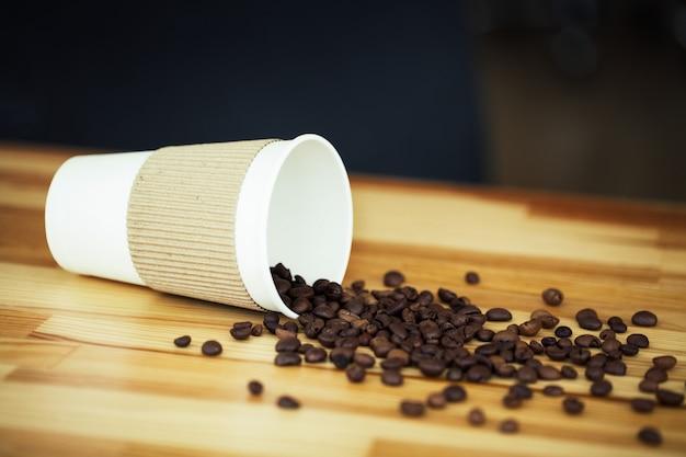 Bonjour. l'heure du café. café à emporter et haricots sur un bois