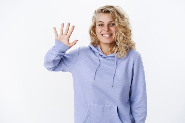 Bonjour heureux de vous rencontrer. blond sortant mignon et sympathique avec une coupe de cheveux courte et des yeux bleus agitant la paume levée dans le geste de salut et de salutation ou disant au revoir souriant agréable à la caméra sur un mur blanc