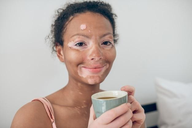 Bonjour. une jeune femme appréciant sa tisane du matin et souriant