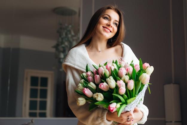 Bonjour! jolie jeune femme avec bouquet de tulipes blanches et roses passe du temps à la maison.
