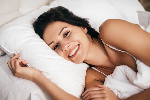 Bonjour! jolie jeune femme souriante et regardant la caméra en position couchée dans le lit à la maison