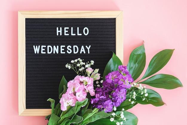 Bonjour mercredi texte sur tableau noir et bouquet de fleurs colorées sur fond rose.