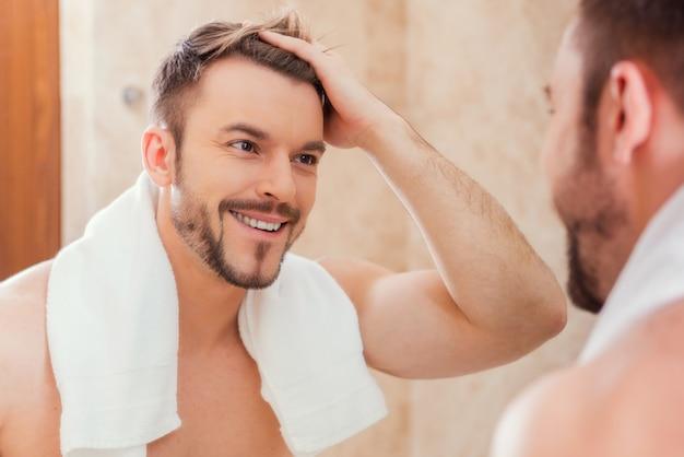 Bonjour à moi. beau jeune homme touchant ses cheveux avec la main et souriant tout en se tenant devant le miroir