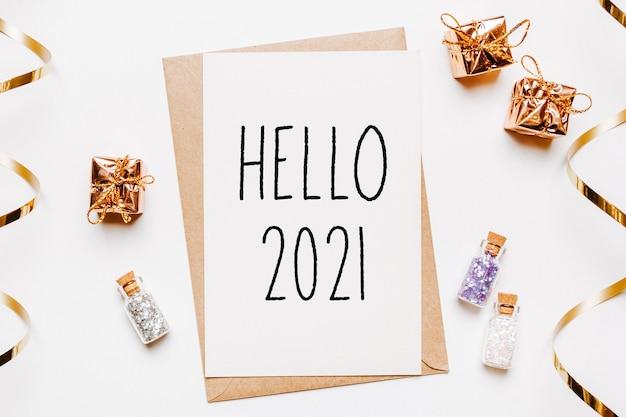 Bonjour note 2021 avec enveloppe, cadeaux et étoiles de paillettes d'or sur blanc.