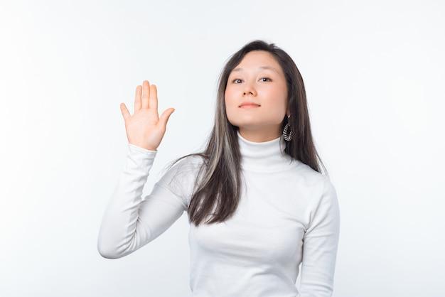 Bonjour. photo de jolie jeune femme montre salut geste sur fond blanc.