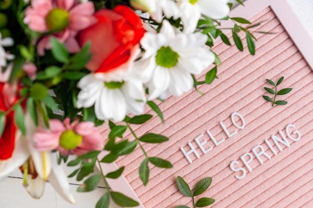 Bonjour printemps sur carton rose et bouquet de fleurs colorées.
