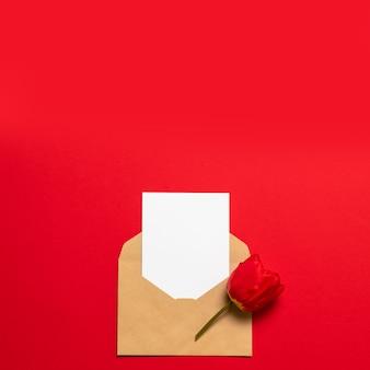Bonjour printemps. dépliant de carte postale vierge blanche avec tulipe rouge, enveloppe d'artisanat, fleur