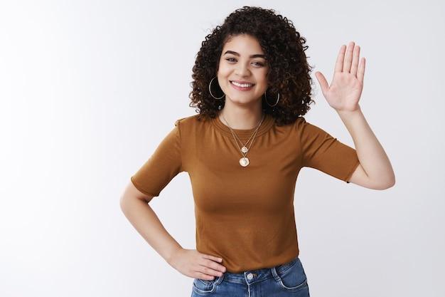 Bonjour salut. une assistante de bureau charmante et sympathique lève la main en agitant un geste de salutation souriant joyeusement détendu tenir la taille de la main rencontrer des gens dire bonjour à un collègue accueillant, fond blanc