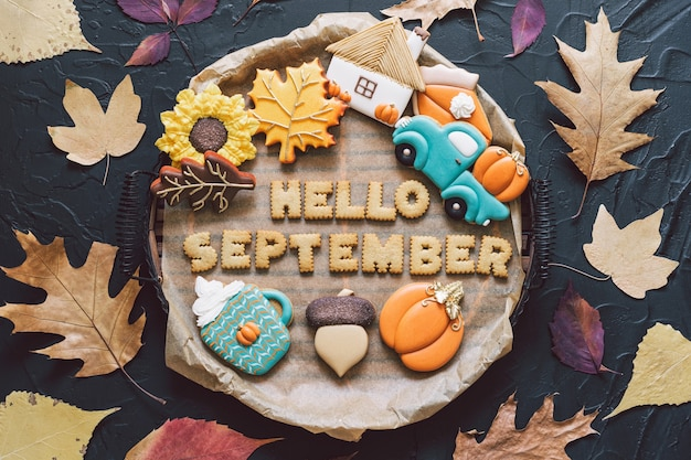 Bonjour septembre. biscuits d'automne multicolores sur fond noir. concept d'automne
