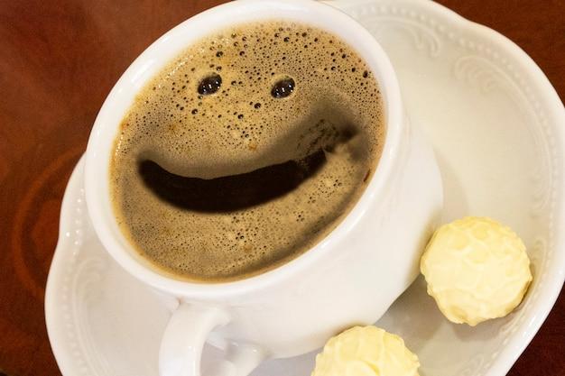 Bonjour, tasse de café blanche avec un sourire et des bonbons sur un fond en bois, gros plan, concept - bonne humeur