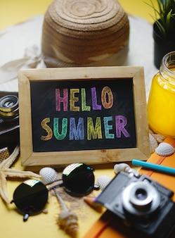 Bonjour texte d'été coloré sur tableau noir entre les accessoires de plage d'été