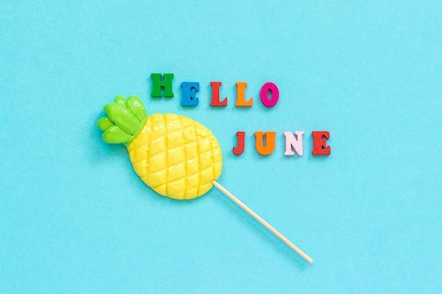 Bonjour texte de juin, sucette ananas sur fond de papier bleu. concept vacances ou vacances