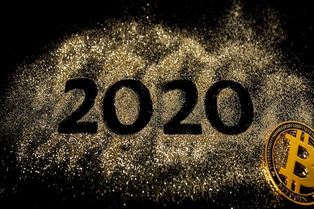 Bonne année 2020. collage créatif des nombres deux et zéro constituant l'année 2020. beau chiffre or pétillant 2020 et bitcoin sur fond noir