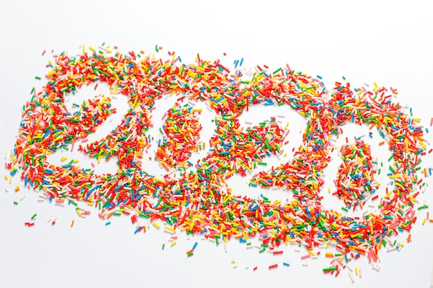 Bonne année 2020. forme de numéro coloré avec des éclaboussures de sucre arc-en-ciel brillant isolé sur blanc