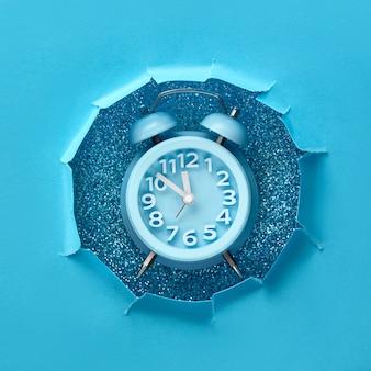 Bonne année 2020! horloge aarm dans le trou de papier, à plat sur la couleur bleue