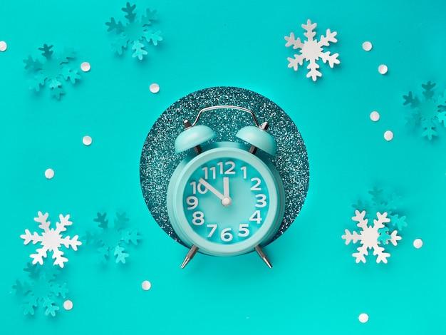 Bonne année 2020! horloge aarm dans le trou de papier, à plat sur du papier de couleur menthe