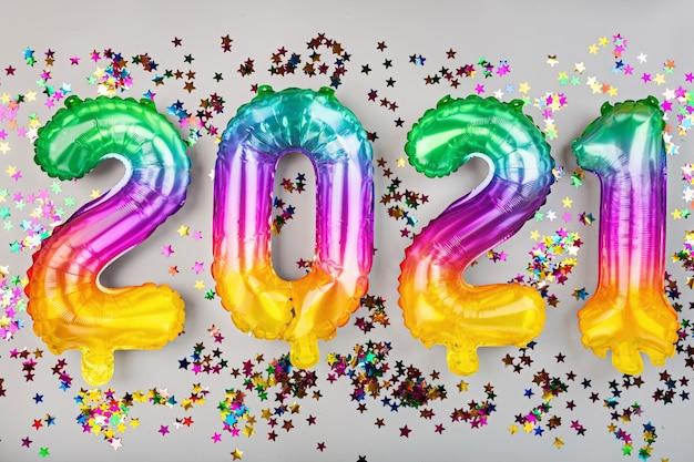 Bonne année 2021. ballons métalliques couleurs arc-en-ciel sur blanc. mise à plat, vue de dessus