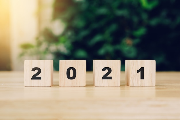Bonne année 2021 sur bloc de bois sur table en bois avec lumière du soleil. concept de nouvel an.