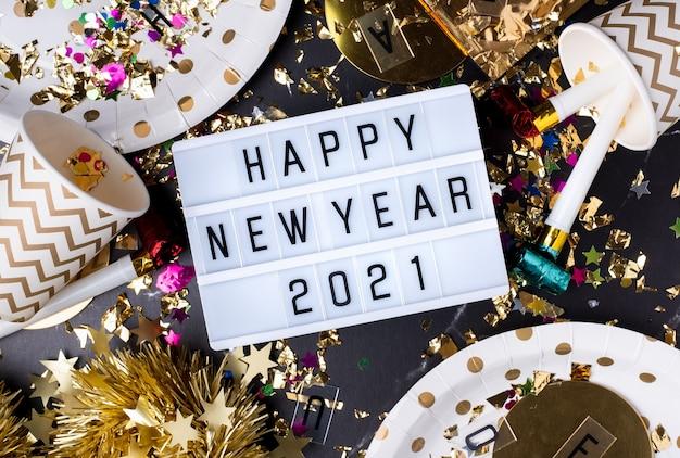 Bonne année 2021 sur boîte à lumière avec tasse de fête, souffleur de fête, guirlandes, confettis