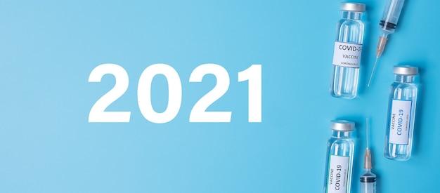 Bonne année 2021 avec le flacon de vaccin covid-19 et la seringue à aiguille d'injection contre le coronavirus