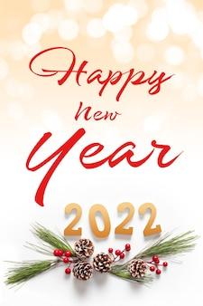 Bonne année 2022. branche de sapin décorée avec des baies et des cônes. concept créatif pour carte de voeux de nouvel an. texte de bonne année.