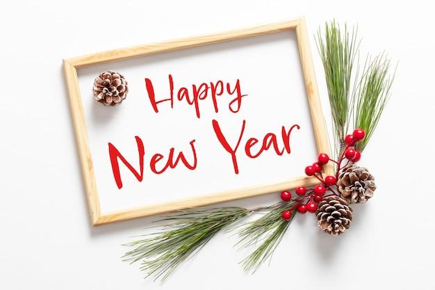 Bonne année 2022. cadre décoré d'une branche de sapin avec des baies et des cônes. concept créatif pour carte de voeux de nouvel an. mise à plat, vue de dessus texte de bonne année.