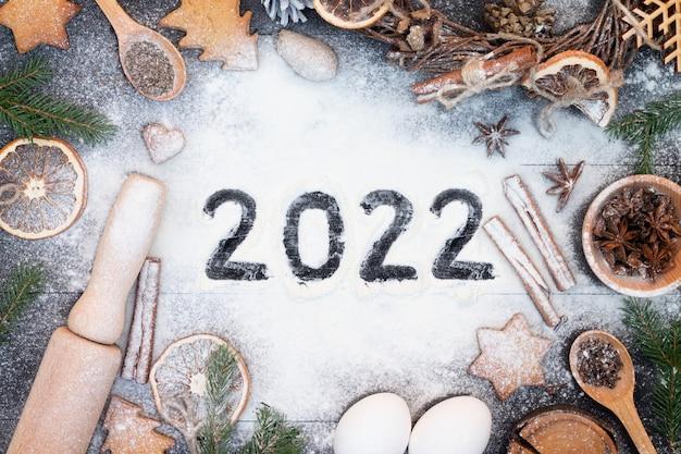 Bonne année 2022 écrite sur la farine. branches d'arbres de noël, biscuits au pain d'épice, épices et produits de boulangerie sur fond de bois noir. noël, carte de voeux de nouvel an