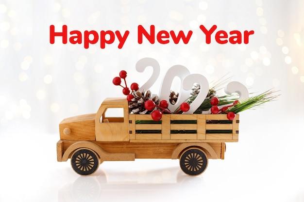 Bonne année 2022. petite voiture en bois avec des baies et des cônes. concept créatif pour carte de voeux de nouvel an. texte de bonne année.
