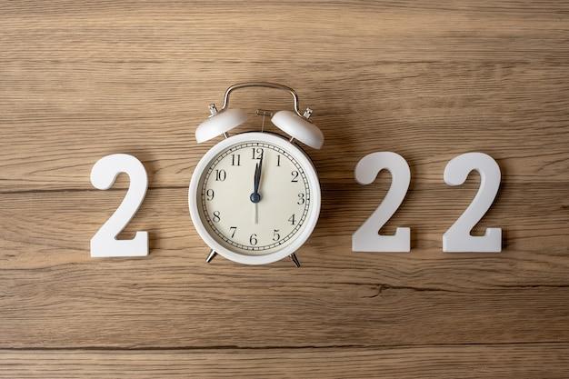 Bonne année 2022 avec réveil rétro et numéro en bois. joyeux noël, nouveau départ, résolution, compte à rebours, objectifs, plan, action et concept de mission