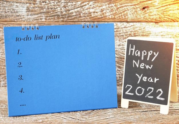 Bonne année 2022 signe de tableau noir et liste de plans de calendrier à faire pour le fond