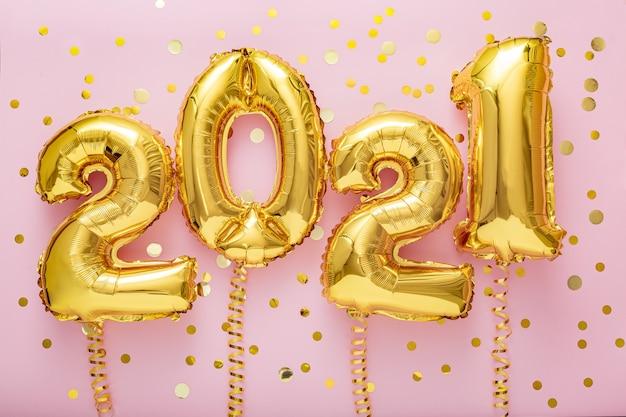 Bonne année ballons en feuille d'or 2021 ballon sur rose avec des confettis.