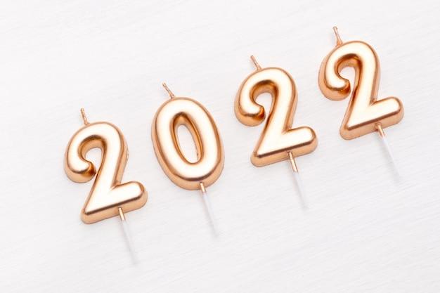 Bonne année et célébration de noël festif nombre d'or bougies noël sur fond blanc