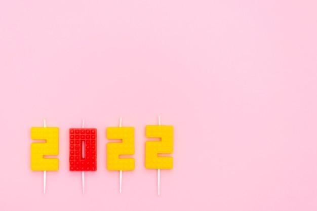 Bonne année et fête de noël bougies numéro festif noël sur fond rose