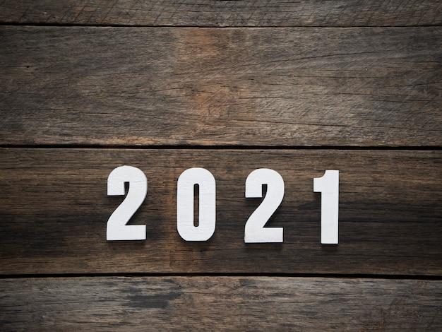 Bonne année fond avec 2021 chiffres sur fond en bois foncé rustique. espace pour le texte