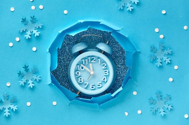 Bonne année! horloge aarm dans le trou de papier, vue de dessus à plat sur papier bleu avec de la neige et des flocons