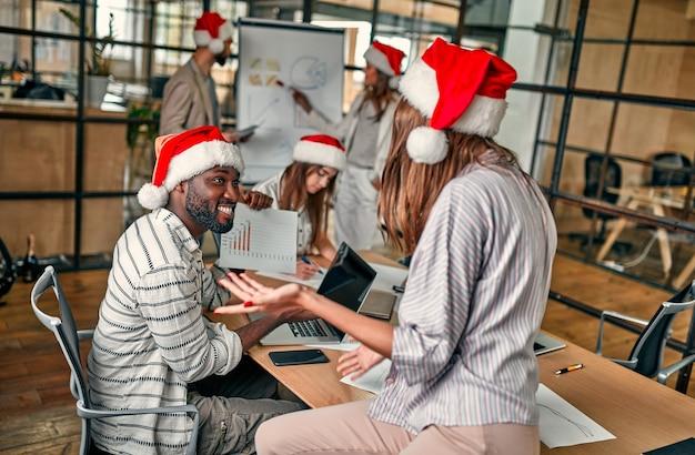Bonne année et joyeux noël! les jeunes créatifs multiraciaux travaillent dans un bureau moderne. un groupe de jeunes gens d'affaires sont assis dans des chapeaux de père noël lors de leur dernier jour de travail.