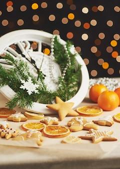 Bonne année à minuit, vieille horloge en bois avec des lumières de vacances et des branches de sapin. cuisiner et décorer des biscuits de pain d'épice de noël et des tranches d'orange frites