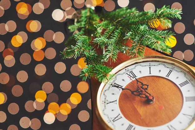 Bonne année à minuit, vieille horloge en bois avec des lumières de vacances et des branches de sapin